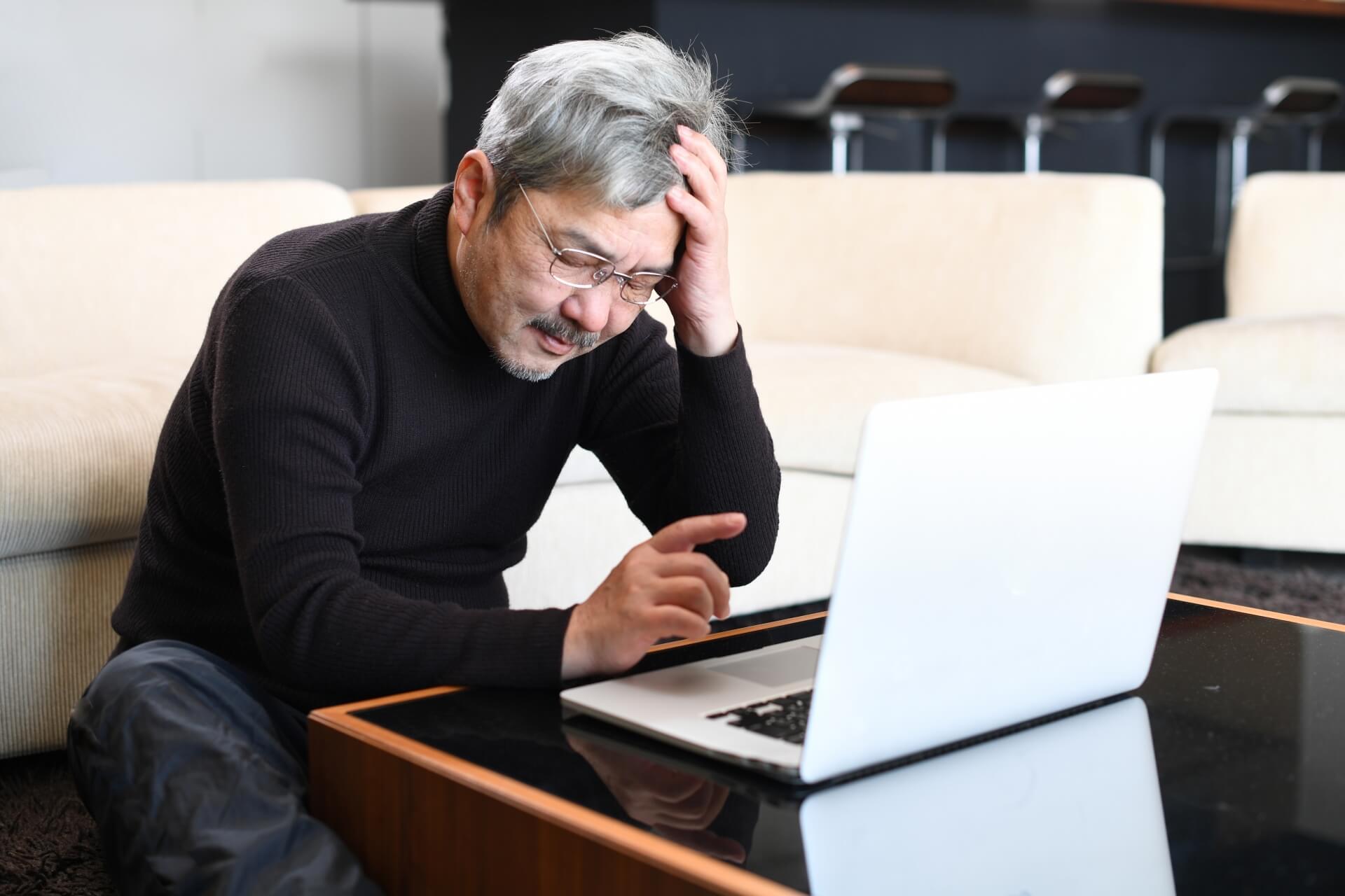 パソコンの前で悩む高齢者の男性